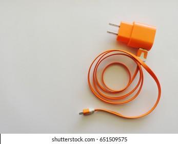 Orange phone charger on white background.