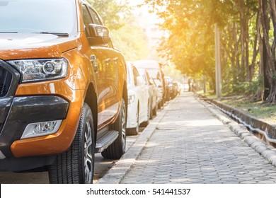 Orange pickup truck car parked in the parking lot beside the sidewalk.