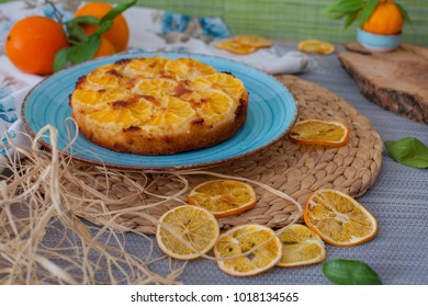 Orange pie on blue plate with dried citrus