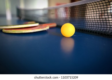 An orange ping pong ball with a rack on the table. To practice