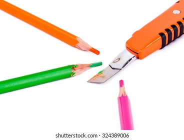 Orange, pink and green pencils and cutter are on isolated whote background
