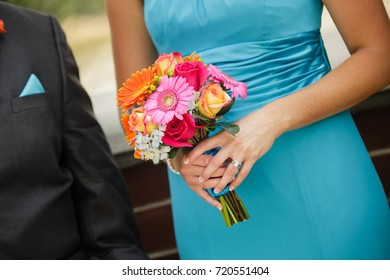 An orange, pink, red, yellow bouquet being held by a bridesmaid wearing a blue dress walking down the aisle with a groomsman.