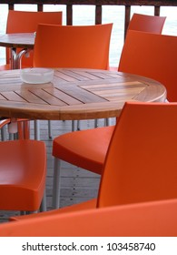 Orange plastic chairs and wooden tables in an outdoor bar