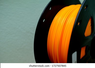 Orange plastic filaments with for 3D Printer.3d printing filament spool or coil on holder on green background. Colored plastic material for 3d printer.orange color