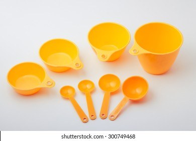 Orange plastic measurement cups and spoons isolated on white background.