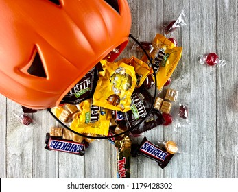 Orange plastic pumpkin bucket with spilled Halloween candy on a wood surface
