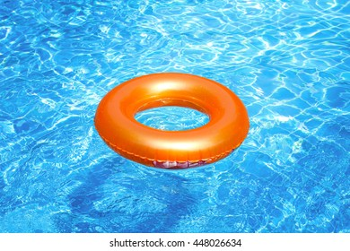 Orange pool float, ring floating in a refreshing blue swimming pool