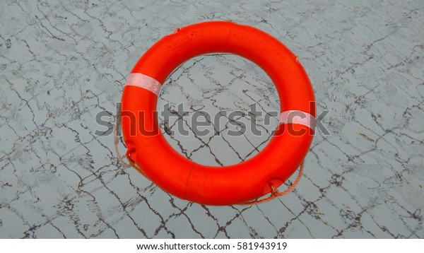 Orange pool float, ring floating in a refreshing blue swimming pool