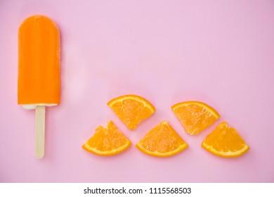 orange popsicle with few slice of orange on a pink background