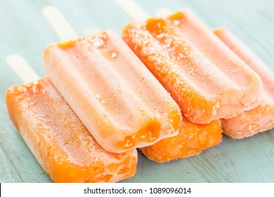 Orange Popsicle snack treats stacked on blue wood background in summertime