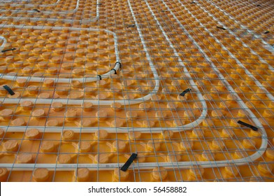Orange posed Underfloor heating tube in a construction site