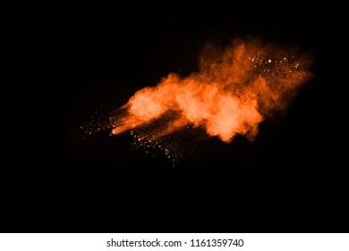 Orange powder explosion on black background. Colored cloud. Colorful dust explode. Paint Holi.