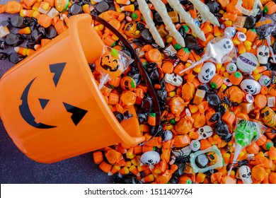 Orange pumpkin bucket spilling Halloween candy on black stone surface with skeleton hands grabbing candy