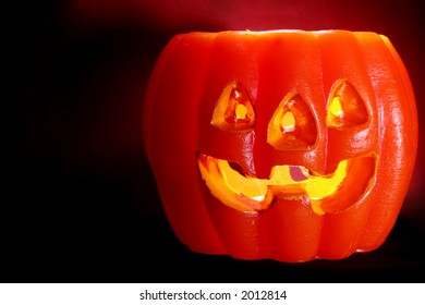 Orange pumpkin face on dark background with illumination from within