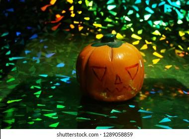 Orange pumpkin for halloween on holografic paper.