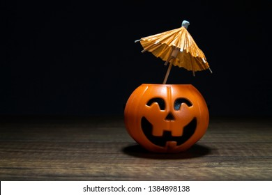 Orange Pumpkin Halloween with umbrella on wooden table in black background