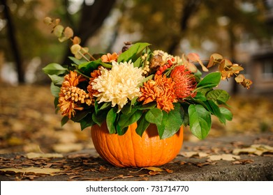 Orange pumpkin with a lovely autumn flower composition on the background of yellow fallen leaves