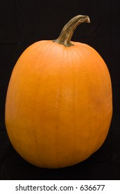 orange pumpkin, ready to be carved into a jack-o-lantern, on black background.