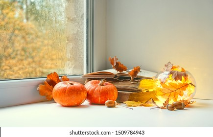 orange pumpkins, books and candle lantern on window sill. beautiful autumn seasonal composition. fall time, thanksgiving and halloween concept. home comfort. copy space