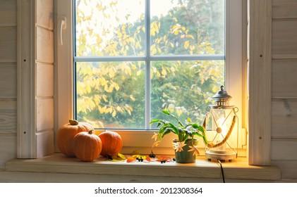 Orange pumpkins on windowsill, candles, autumn leaves and lantern. Scandinavian style.