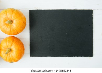 Orange pumpkins on wite wooden background and black slate stone surface. Thanksgiving and Halloween concept. View from above. Top view. Copy space for text and design