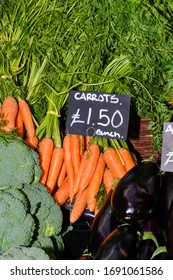 Orange, purple carrots.Local produce for sale displayed at the market. Borough farmer's market in London. Organic and bio fresh healthy eating concept.Veggies, vegetables, herbs and spices, price tags