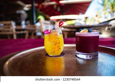 Orange and Purple cocktails on a beaten copper tray sat on a purple cloth in an outdoor bar