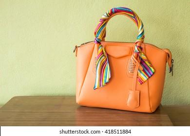 orange purse on wood background, luxury women accessory