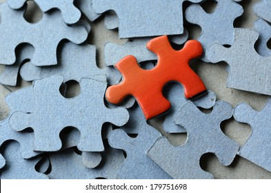 Orange puzzle piece standing out of the rest of puzzle pieces. Conceptual photograph to display business, personal, financial success, or a leadership concept. No people. Copy space