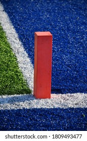 Orange pylon in the end zone of a football field
