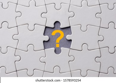 Orange question mark placed on last piece of jigsaw puzzle