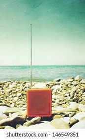 Orange radio set on the beach as old photography.