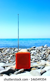Orange radio set on the beach.