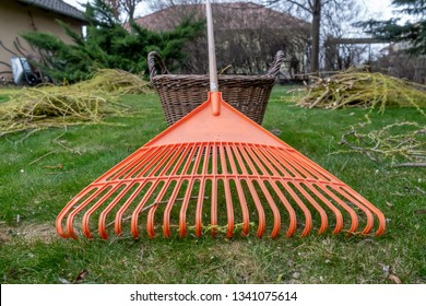 Orange rake next to a basket in the garden