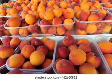 Orange and red apricots in little plastic containers on the market stall close-up.