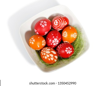 Orange and red Easter eggs on white plate