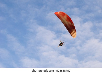Orange and red parachute with a sportsman flying over a blue sky with clouds in summer shorts