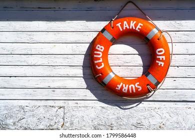 Orange Rettungsfloat. Lifebuoy an der Wand des Gebäudes der Rettungsstation.