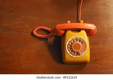 Orange retro telephone on wood
