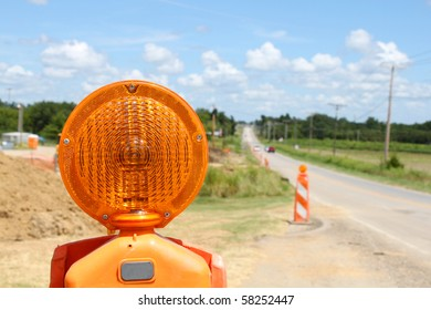 Orange road construction flashers on a long country road