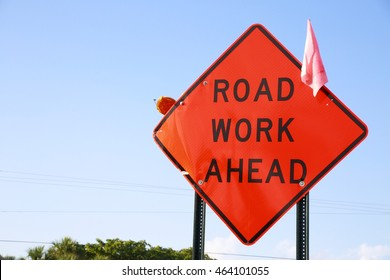 Orange Road Work Ahead Diamond Shaped Sign Frame Right with Clear Blue Sky and Trees Behind