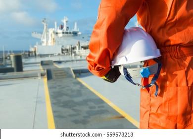 Orange robe engineer with helmet on the deck of oil tanker.