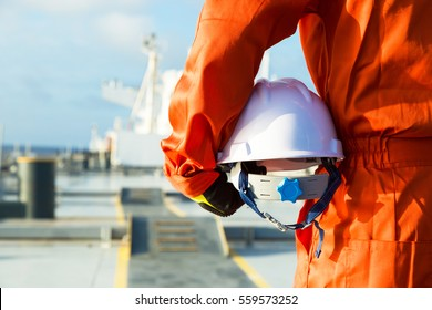 Orange robe engineer with helmet on the deck of oil tanker.