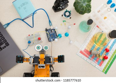 Orange robot and an electronic board that can be programmed. Robotics and electronics. Laboratory in the school. Mathematics, engineering, science, technology, computer code. STEM education for kid.