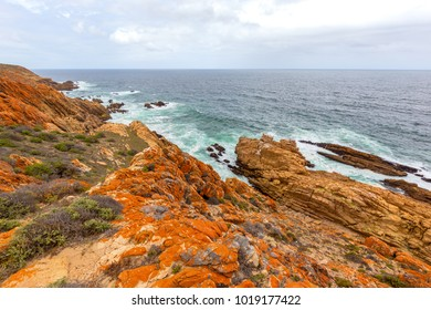 orange rocky shoreline looking over a rough sea and clouded sky