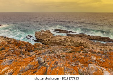 orange rocky shoreline looking over a warm rough sea clouded sky and warm horizon