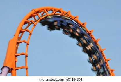 Orange rollercoaster with fast moving carriage
