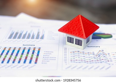Orange roof house Placed on the graph or business data. Concept of business growth Economic charts, real estate markets, mortgages, home taxes, high profits for business investment and financial funds