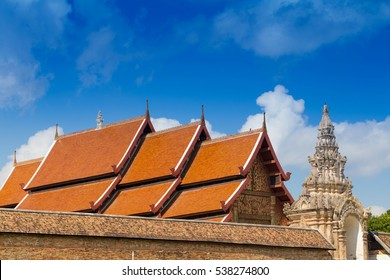 Orange roof of main hall and carved stone sculpture guarding decorate the door roof of lanna style ancient temple in Wat Phra That Lampang Luang, Lampang, Thailand