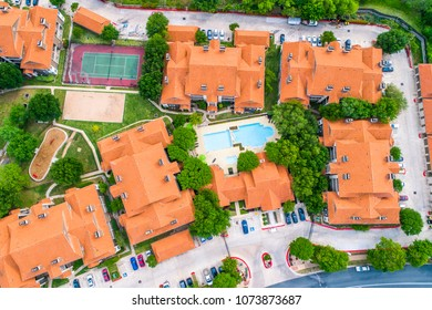 Orange rooftops on new development Apartment townhomes large urban living swimming pool in middle - aerial view - high up straight down view above entire housing complex